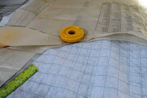Pieces from two different patterns, tru-grid, pattern weights and a ruler.